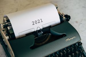 Picture of an old typing machine with a blank page stating 2021
